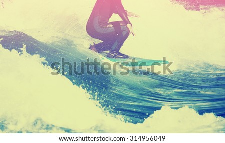 male surfer riding a wave on a white water river park with a toned vintage instagram filter - stock photo