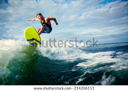 Male surfer riding on waves in the sea - stock photo