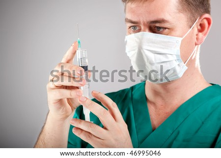 male surgeon holding syringe with vaccine - stock photo