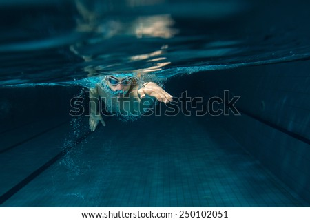 Male swimmer at the swimming pool.Underwater photo. - stock photo