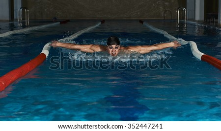 Male swimmer performing butterfly stroke in the pool. Young sportsman in swimwear exercising in the water. - stock photo