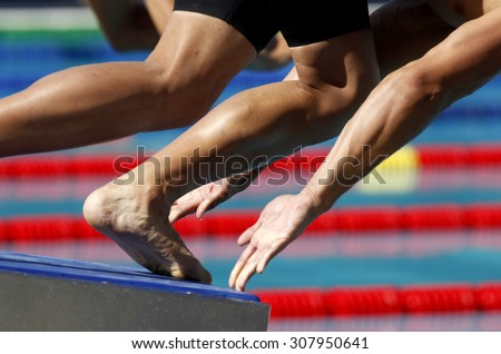 Male swimmer starting swim event jumping into the water - stock photo