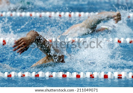 Male swimmer swimming crawl in a competition swim pool - stock photo