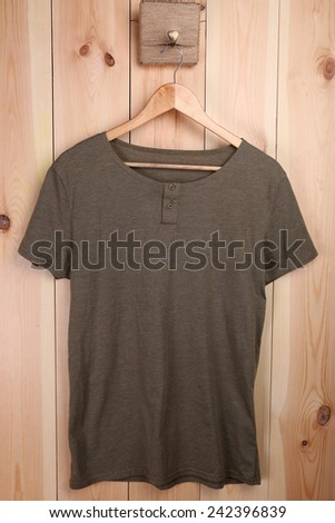 Male t-shirt on hanger on wooden wall background