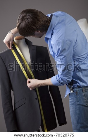 male tailor by the work on business jacket - stock photo