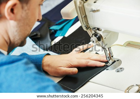 male tailor working with sewing machine and cloth in workshop - stock photo