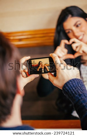 Male Taking A Photo Of His Girlfriend Who Formed A Heart With Her Hands - stock photo
