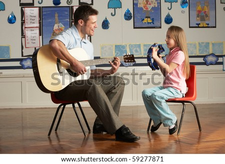 Male Teacher Playing Guitar With Pupil In Classroom - stock photo