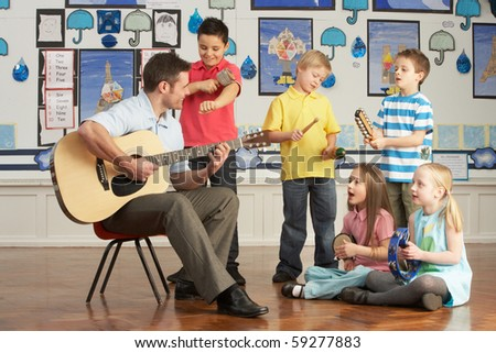Male Teacher Playing Guitar With Pupils Having Music Lesson In Classroom - stock photo