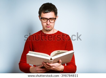 Male teacher reading a book, isolated on a gray background - stock photo