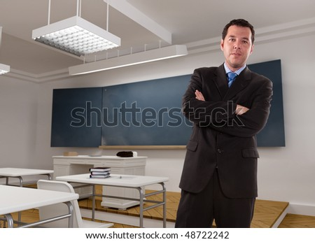 Male teacher smartly dressed in an empty classroom - stock photo