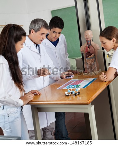 Male teacher teaching experiment to teenage high school students at desk in lab - stock photo