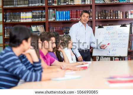 Male teacher with a group of college students in class