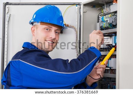 Male Technician Examining Fusebox With Digital Insulation Resistance Tester