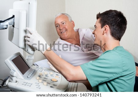 Male technician showing ultrasound machine's monitor to senior patient - stock photo