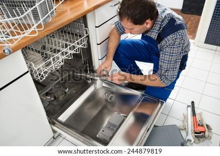 Male Technician Sitting Near Dishwasher Writing On Clipboard In Kitchen - stock photo
