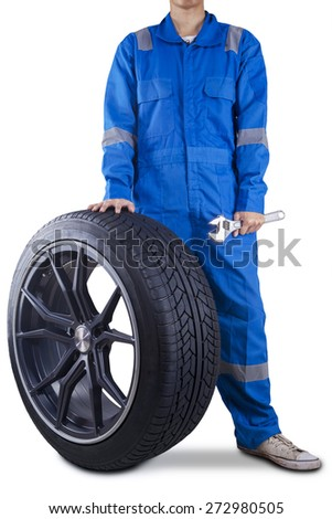 Male technician with a blue uniform holding a black tire and wrench, isolated on white - stock photo