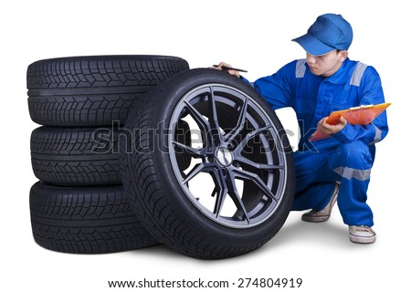 Male technician with a blue uniform, holding a clipboard while checking tires - stock photo