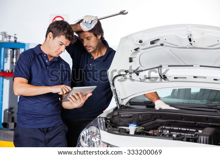 Male technicians using digital tablet by car with open hood at auto repair shop - stock photo