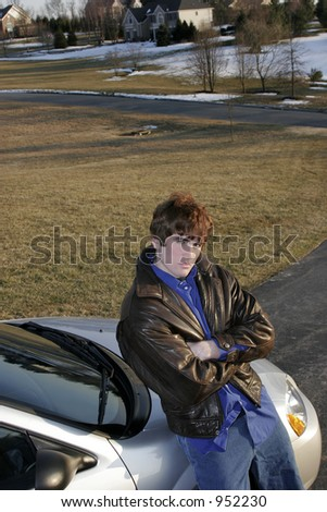 male teen leaning on auto with attitude - stock photo