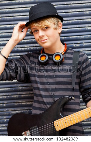 male teen musician portrait outdoors with guitar - stock photo
