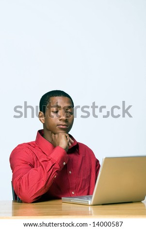 Male teen student appears bored while he works on his laptop computer. Vertically framed photograph