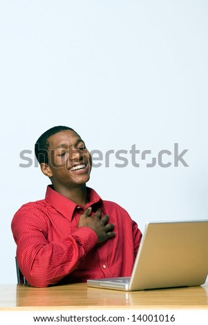 Male teen student laughs while he looks at his laptop computer. Vertically framed photograph