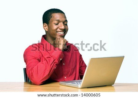 Male teen student laughs while he works on his laptop computer. Horizontally framed photograph - stock photo