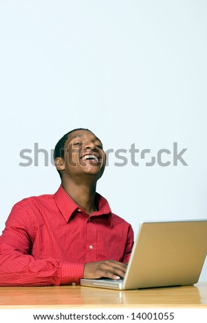 Male teen student laughs while looking at the camera as he works on his laptop computer. Vertically framed photograph