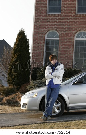male teen youth leaning on new car in driveway of upscale home - stock photo
