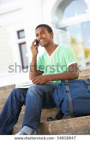 Male Teenage Student Sitting Outside On College Steps - stock photo