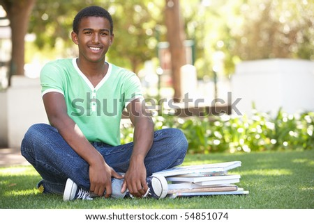 Male Teenage Student Studying In Park - stock photo