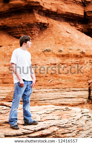 male teenager in mountains, standing on rock. Holes in jeans, hands in pocket, looking into distance.