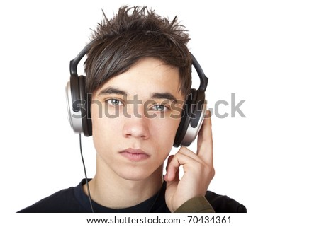Male Teenager with headphone listening seriously to language cd. Isolated on white background. - stock photo