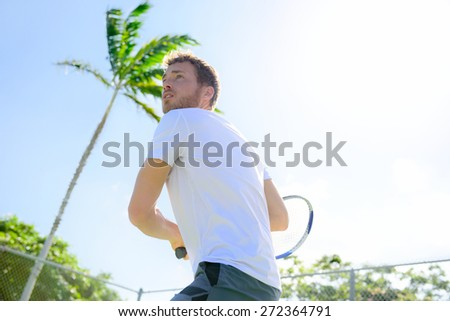 Male tennis player finishing serve playing outdoor. Man serve for game during outside tennis game. Fit male athlete living healthy fitness sport lifestyle. Young Caucasian model in his 20s. - stock photo