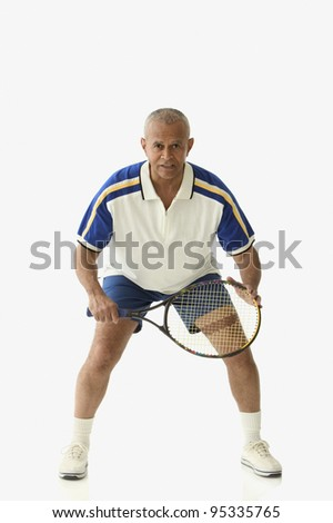 Male tennis player in defensive stance - stock photo
