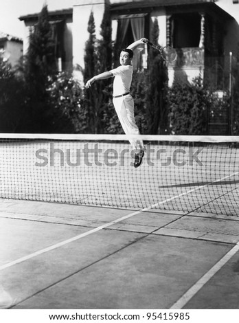 Male tennis player jumping for shot - stock photo