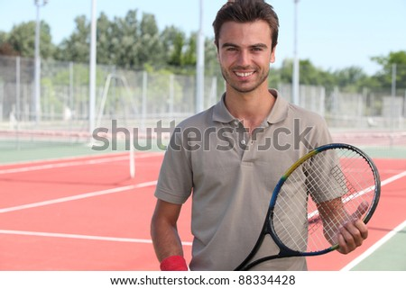 Male tennis player on a hardcourt - stock photo