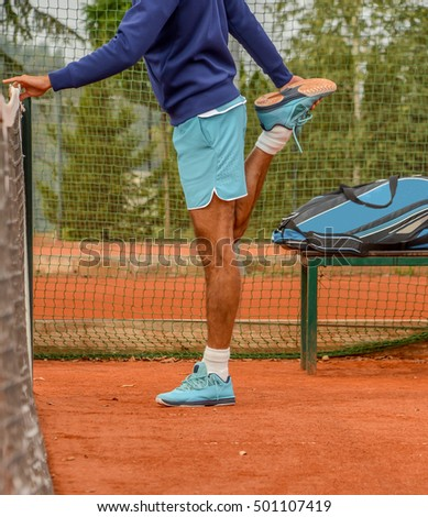 male tennis player stretching before playing