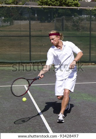 Male tennis player takes a forehand swing at the ball - stock photo