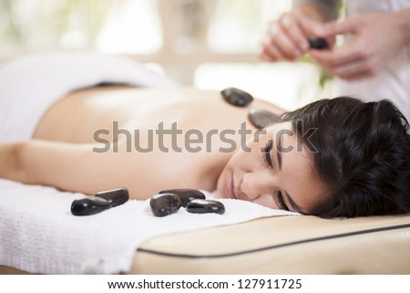 Male therapist applying some heat with hot stones during a massage - stock photo