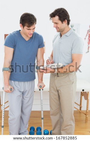 Male therapist discussing reports with a disabled patient in the gym at hospital - stock photo