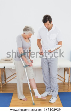 Male therapist examining disabled senior patient' leg in the gym at hospital - stock photo