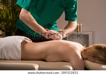 Male therapist tapping young woman's skin during massage - stock photo