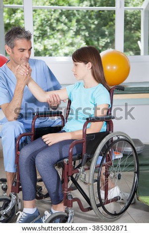 Male therapist with girl in wheelchair - stock photo