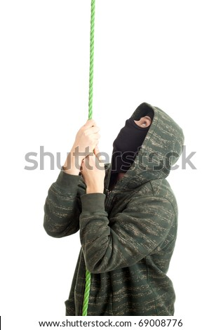 male thief in mask and hood climbing on rope - stock photo