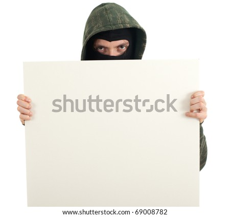 male thief in mask and hood with blank sign, billboard - stock photo