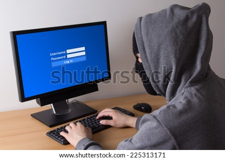 male thief in mask log in to computer - stock photo