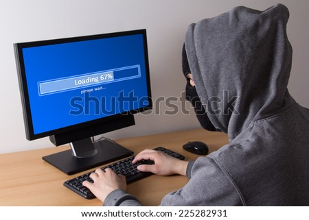 male thief in mask stealing data from computer - stock photo