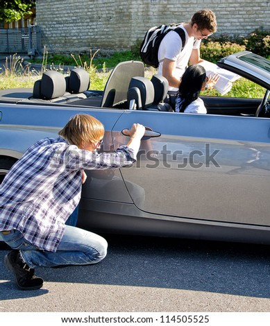 Male thief opening car door while his accomplice distracts female driver - stock photo